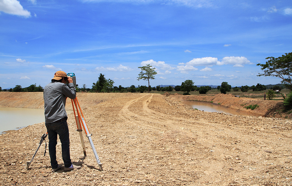 Land, man takes photo of building site